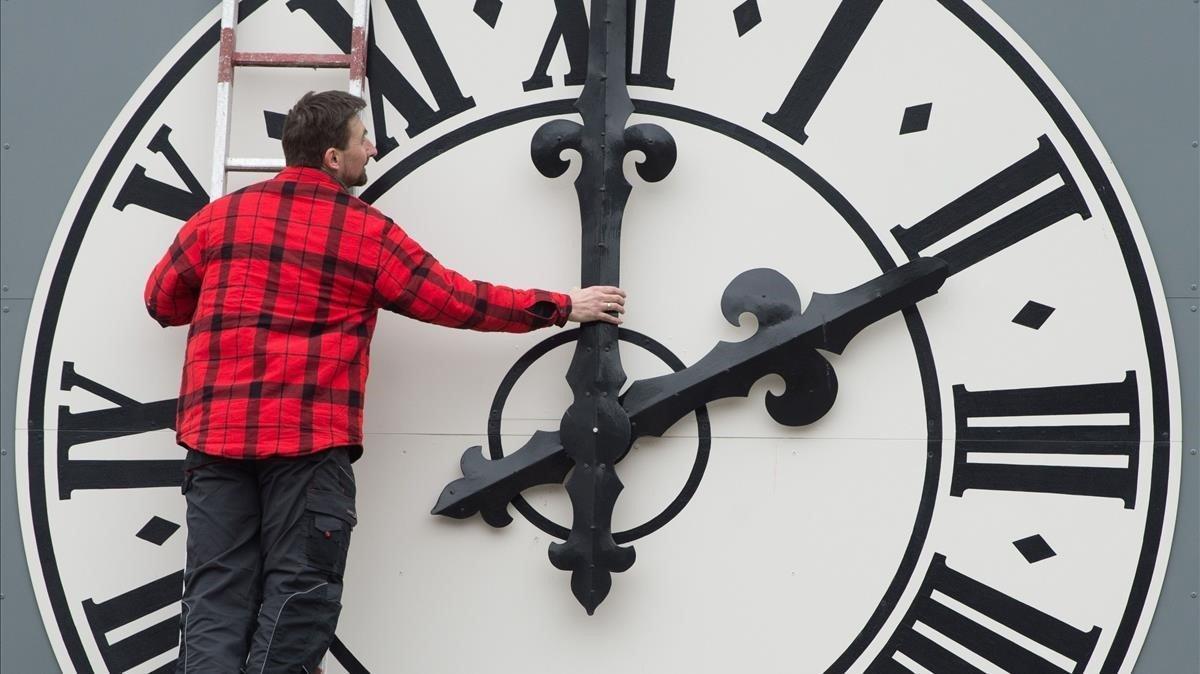 Un operario cambia las manecillas del reloj de una iglesia de Dresde, en Alemania.