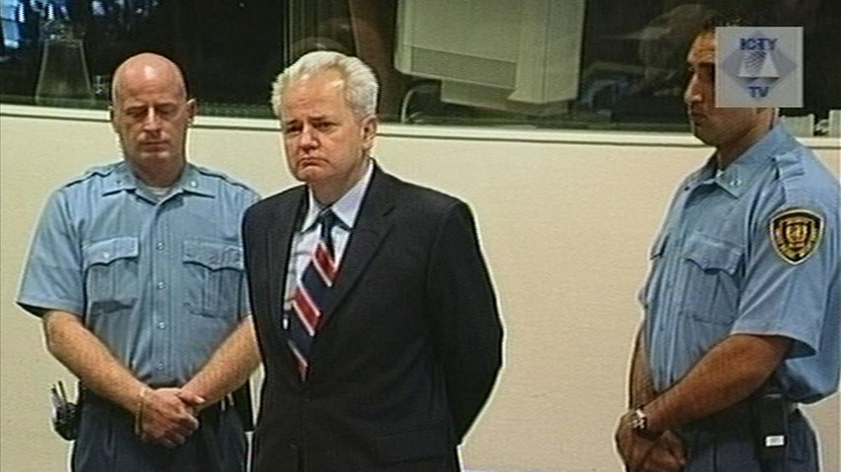 Slobodan Milosevic (centro), expresidente de Serbia, junto a dos guardias de seguridad antes de comparecer en el TPIY, en La Haya, el 3 de julio del 2001.