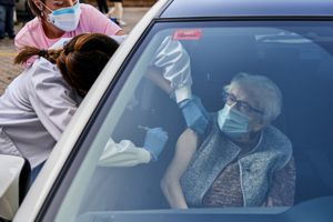 Una mujer de más de 80 años recibe una vacuna dentro de un coche en Vitoria.
