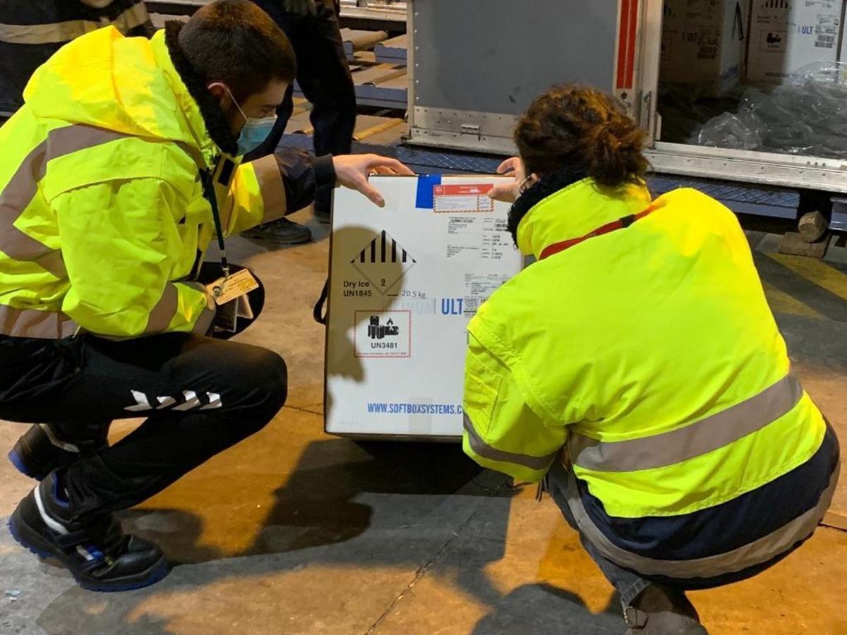 Dos operarios examinan las cajas de las vacunas de Pfizer, en el aeropuerto de Vitoria.