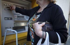 Una dona gran aguanta el seu moneder mentre treu diners d'un caixer a Barcelona.
