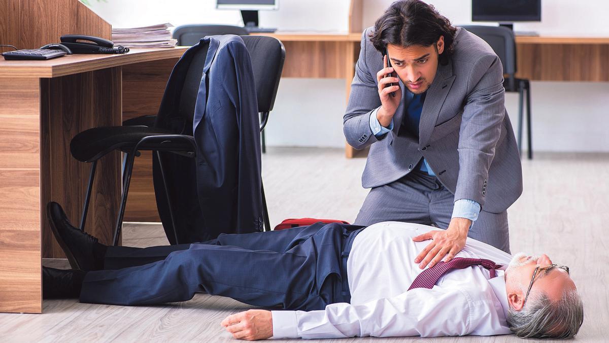 Una persona atiende a un compañero de trabajo que ha sufrido un infarto.