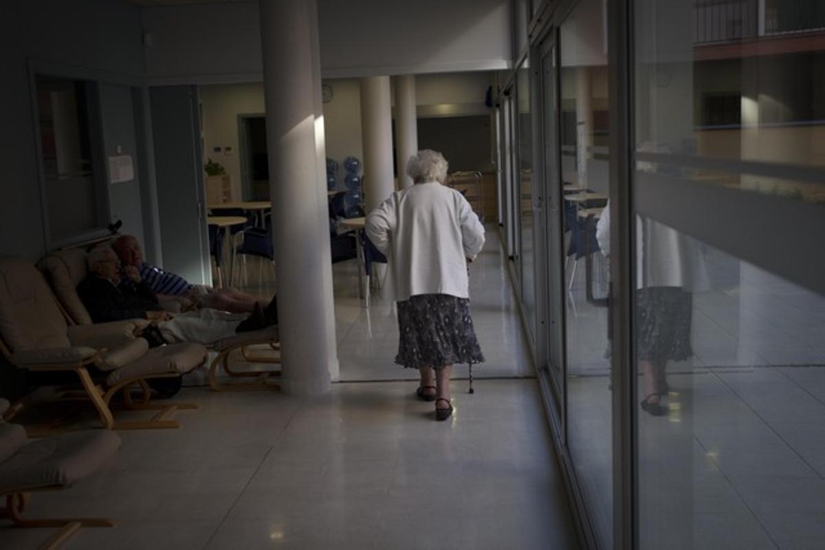 Una anciana camina en soledad por los pasillos de una residencia.