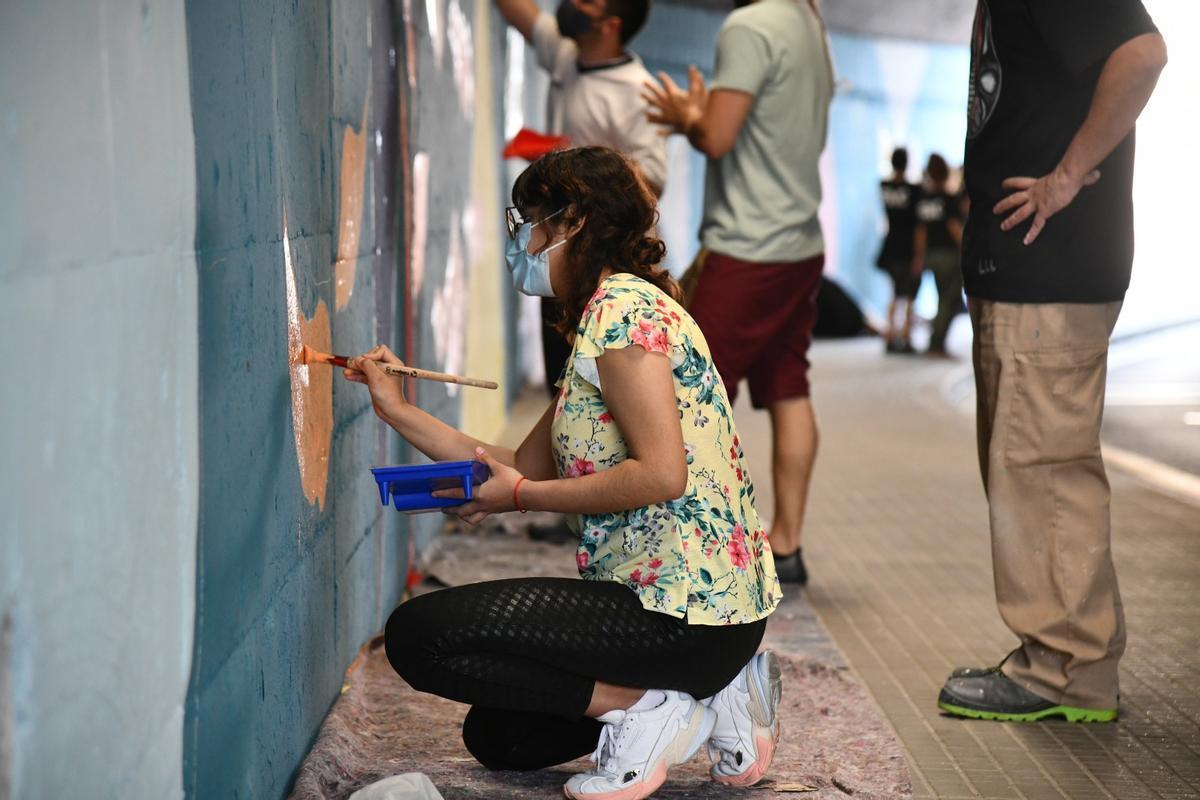 Jóvenes pintan un mural artístico en el túnel de la calle Ignasi Iglesias