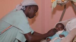 Una mujer cuida a un bebé en Senegal en el refugio de las Hermanas Franciscanas.
