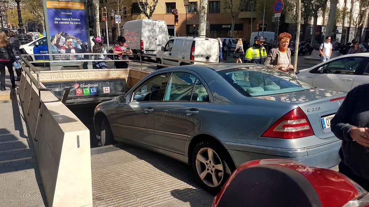 El conductor de un coche confunde la entrada del metro con un párking en el paseo de Gràcia.