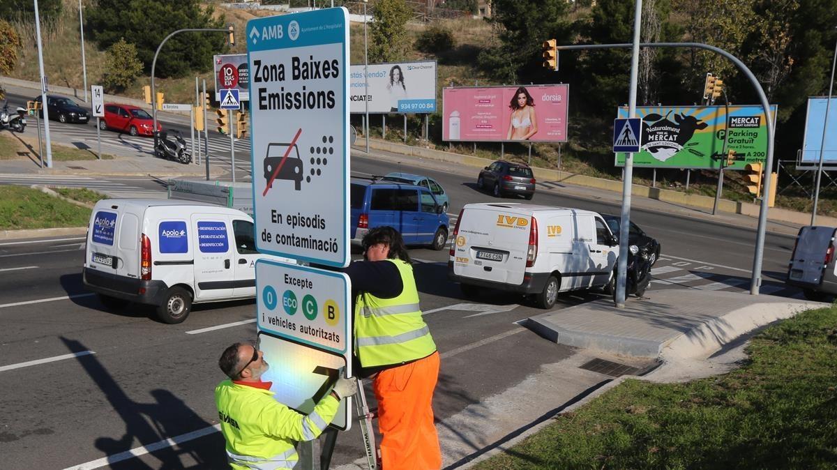 Operarios instalan la señalización de las Zonas de Baja Emisión en el Área metropolitana.