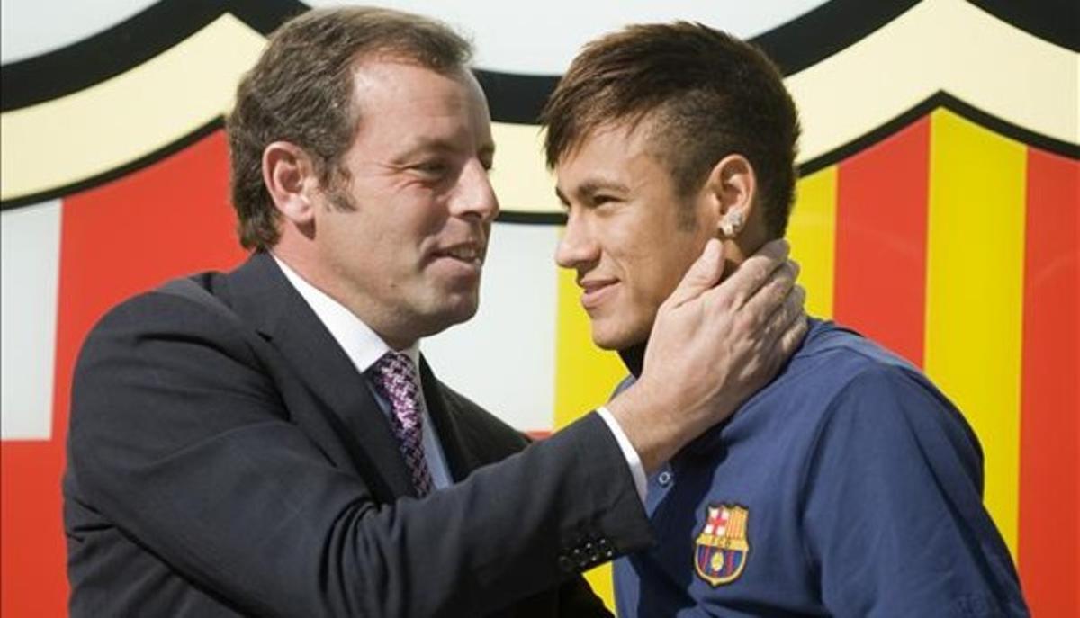 Rosell y Neymar posan ante el escudo del Barça en las oficinas del club el día de la presentación del jugador.