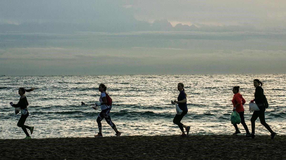 Miembros de Barcelona Plogging, al amanecer en la Barceloneta. Antes de correr, te dan una bolsa biodegradable y un par de guantes. La próxima quedada es el 7 de noviembre.