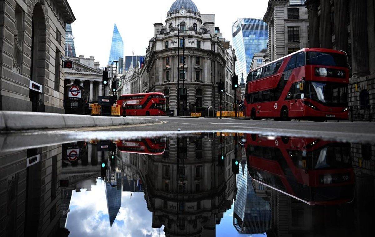 Autobuses pasan frente al Banco de Inglaterra en el distrito financiero de Londres.