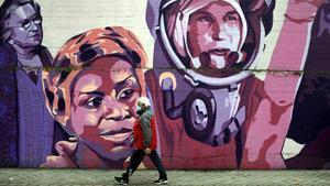 Un hombre pasa por el mural feminista en el polideportivo municipal de la Concepción, en Madrid.