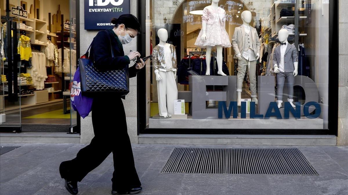 Una mujer pasa frente a una tienda de ropa para niños, este miércoles en Milán.