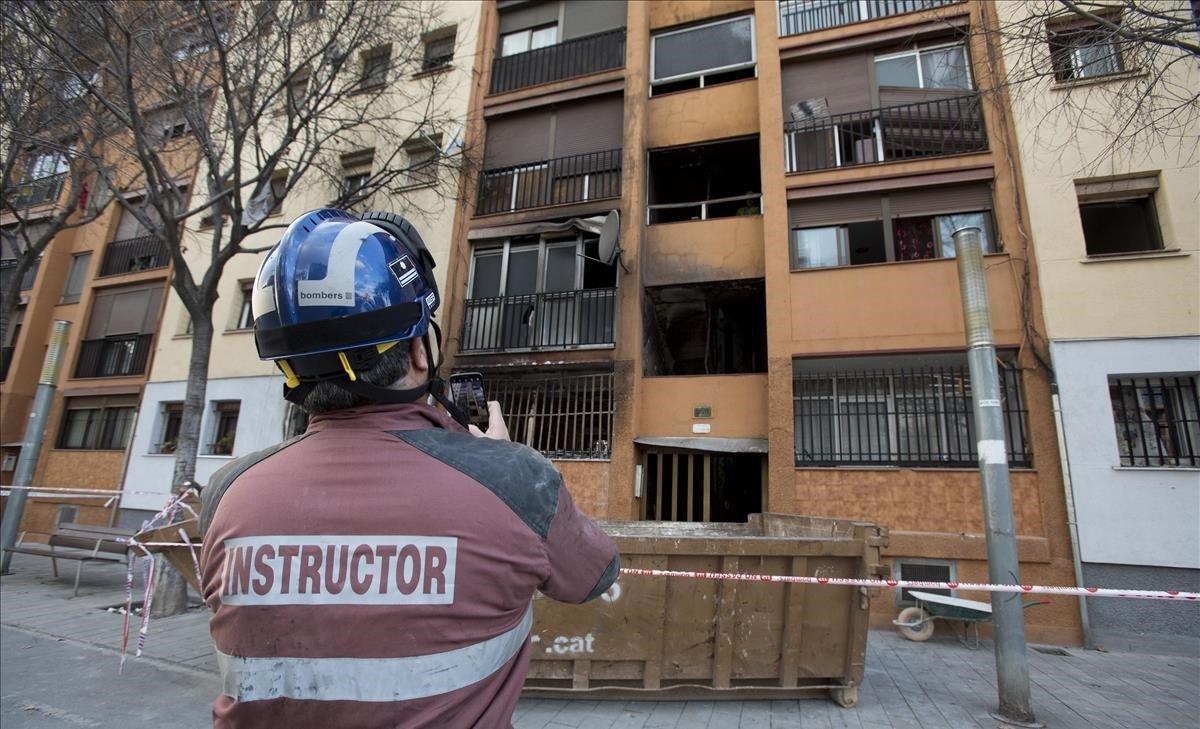Un miembro del equipo de investigación de bomberos examinan el edificio del barrio de Sant Roc de Badalona donde el día 5 se produjo un incendio con tres personas muertas.