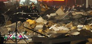 Miembros de los equipos de rescate buscan supervivientes entre los escombros, en Riga,