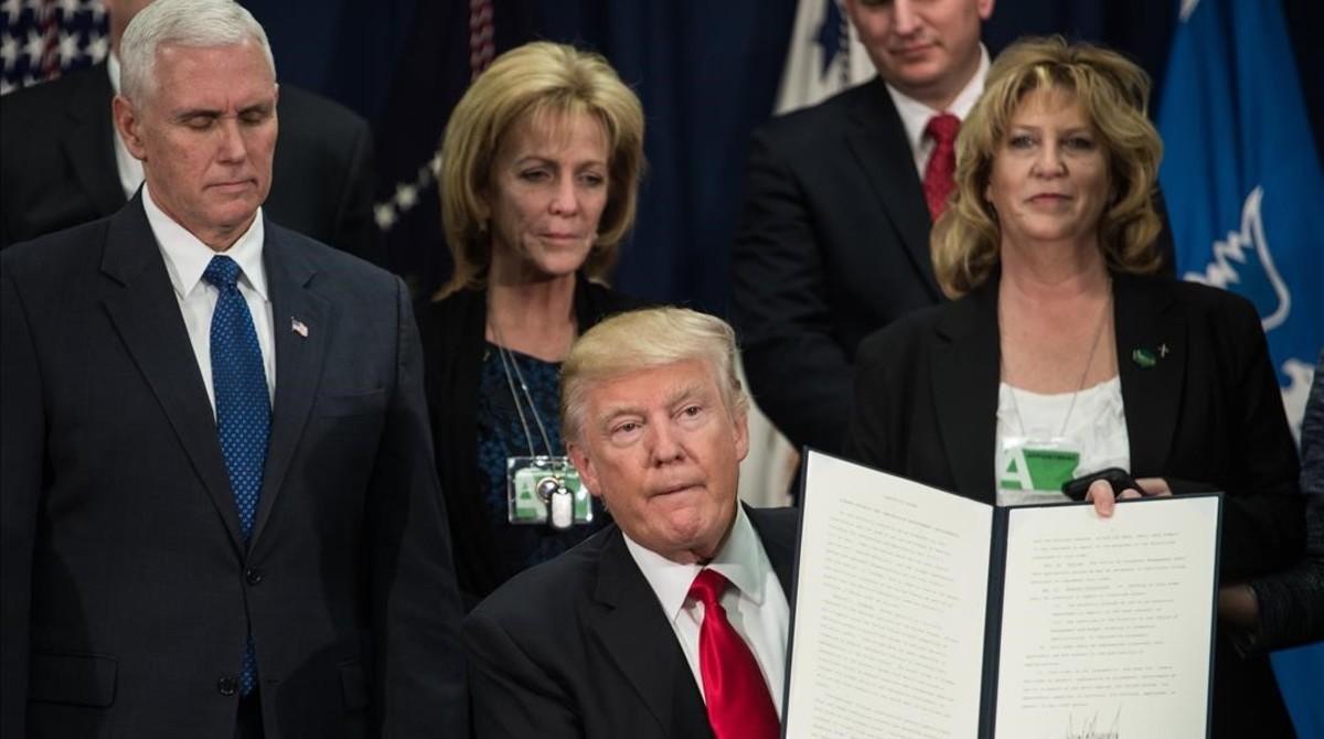 Trump muestra la orden ejecutiva para iniciar el proyecto del muro fronterizo con México, en Washington, este miércoles.