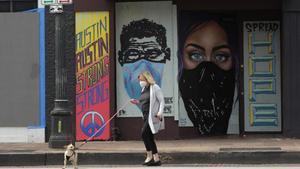 Una mujer pasea a su perro por una calle de Austin (Texas).