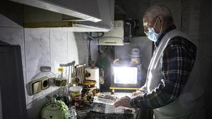 Juan Pérez se ayuda de linternas y un foco a pilas para orientarse en su casa de los cortes de luz que sufre el barrio del Culubret, de Figueres.