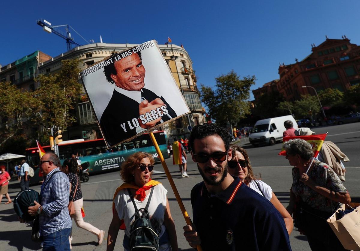 Un manifestante, con una pancarta de un meme con la foto de Julio Iglesias.
