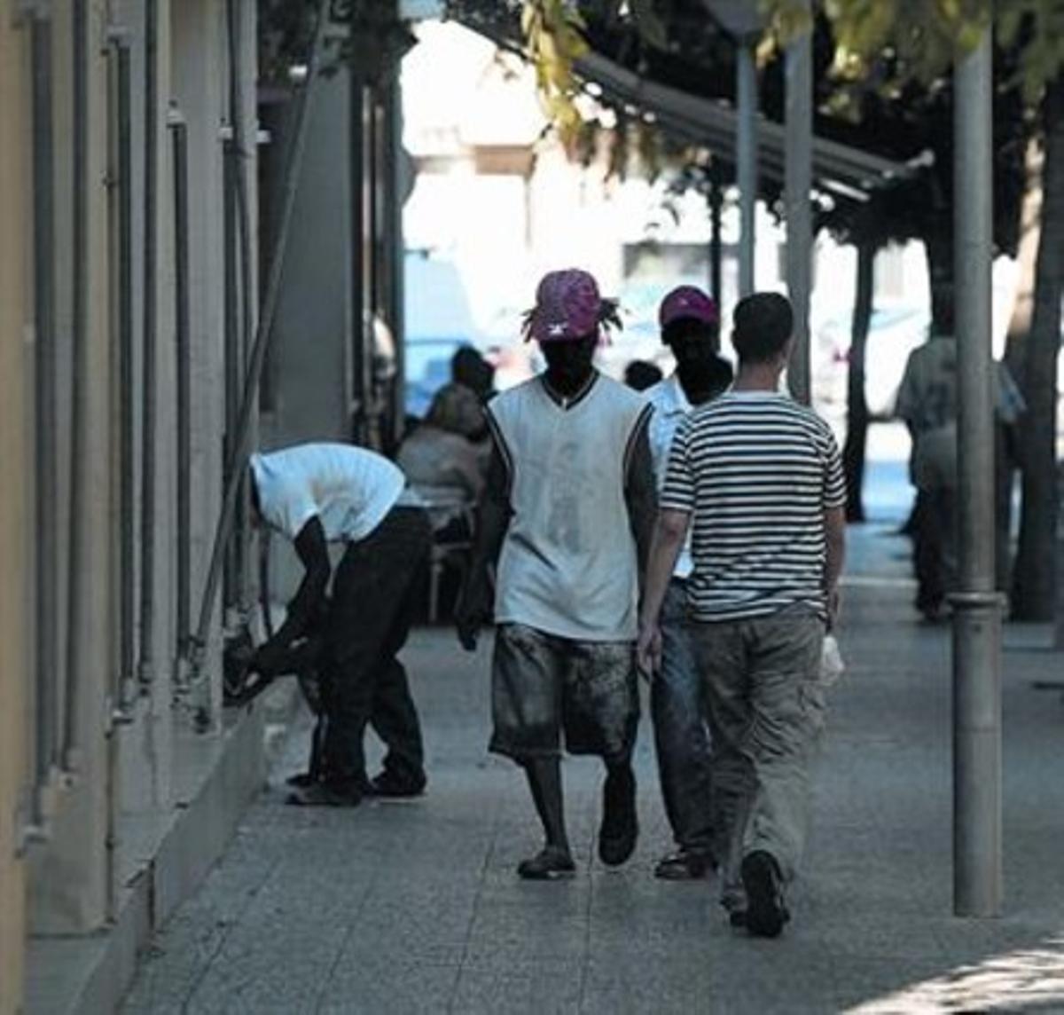 Unos inmigrantes caminan por una céntrica calle de Salt.