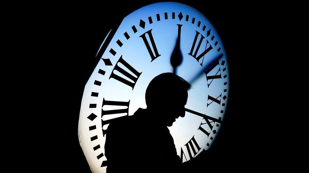 Un hombre paseo con el reloj de la Puerta del Sol al fondo.