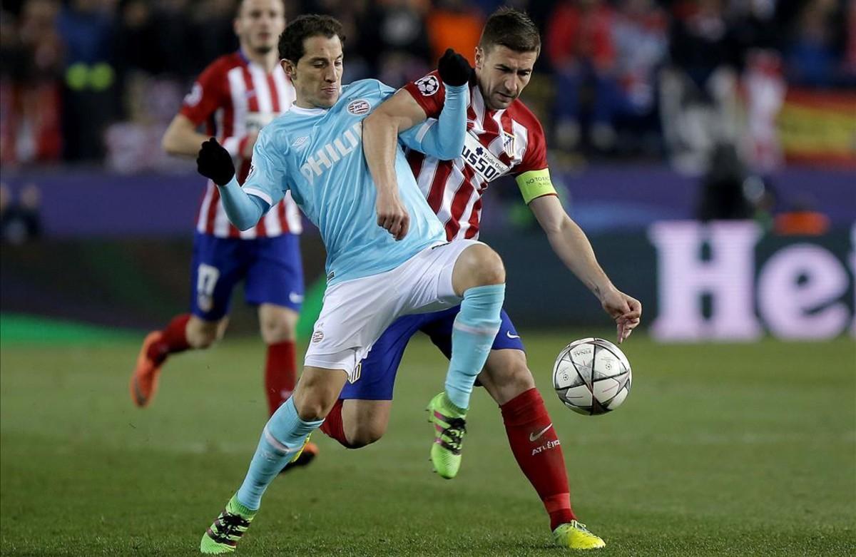 Gabi y el mexicano Guardado disputan elbalón durante el partido entre el Atlético y el PSV.