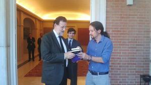 En el primer encuentro entre los dos líderes, el candidato a las presidenciales de Podemos le entrega un libro de Machado a Mariano Rajoy