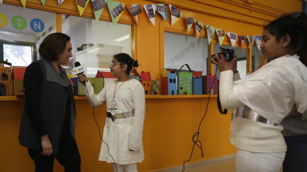 La pequeña Gursimar graba con la cámara mientras su compañera Asima entrevista a la alcaldesa, Ada Colau, este viernes en el Institut Escola Trinitat Nova.