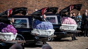 Los ataúdes cubiertos de hortensias de los niños fallecidos.