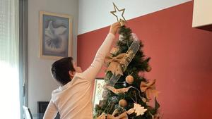 El hijo de la farmacéutica Gemma del Caño coloca una estrella en el árbol de Navidad familiar.