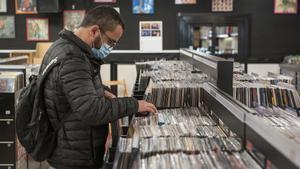 Un cliente busca en las cubetas de vinilos de Disco 100, este viernes.