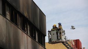 Bomberos revisan la nave ocupada incendiada en Badalona.
