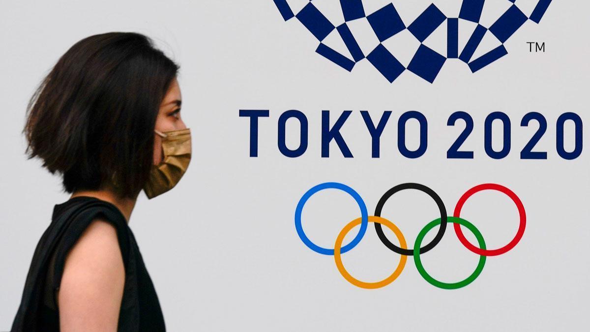 Una mujer pasa junto al emblema de los juegos olímpicos, en una calle de Tokio.