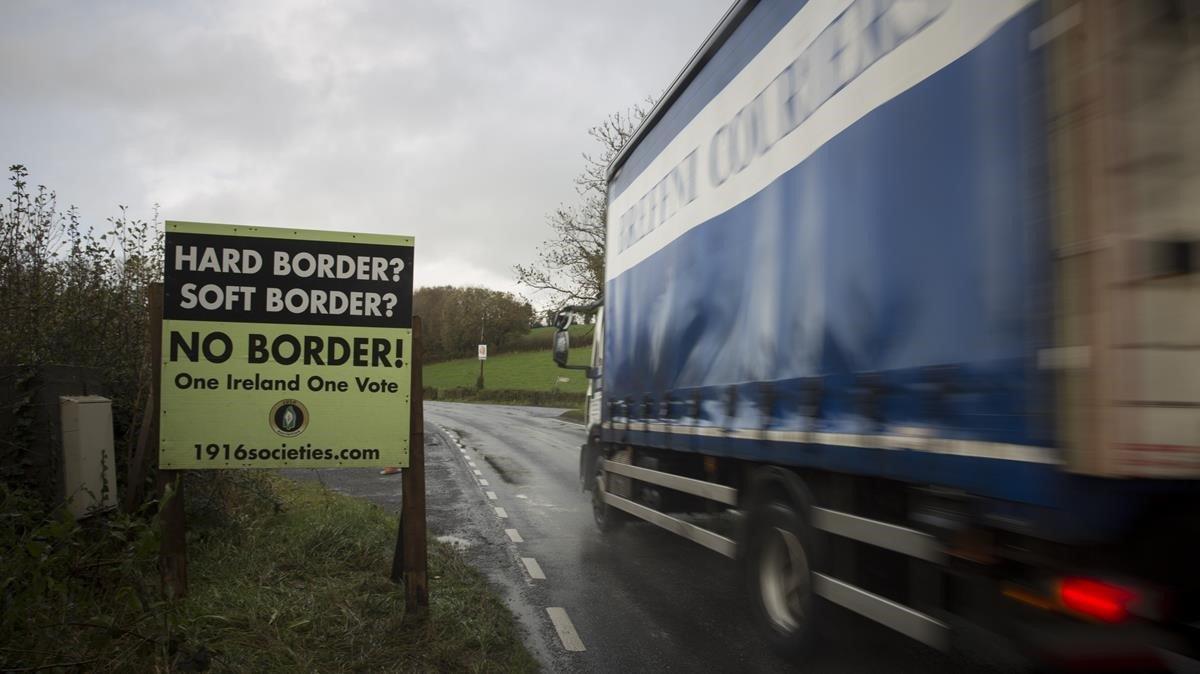 Un camión pasa por un letrero contra la instauración de una frontera física entre la dos Irlandas.