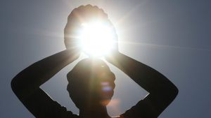 Un sol intenso entre las manos de una estatua del parque del Retiro, en Madrid.