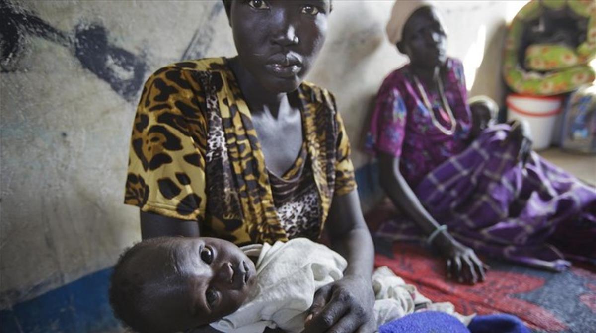 Una mujer sostiene a su hijo en brazos, víctima de la deshidratación, en un hospital de Médicos sin Fronteras en Awerial (Sudán del Sur), el pasado enero.