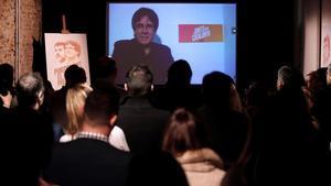 Carles Puigdemont conversa por videoconferencia con candidatos y simpatizantes durante la inauguración de la sede de campaña de Junts per Catalunya.