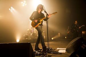 Alex Turner y Jamie Cook (en el fondo), en plena actuación de Artic Monkeys en Barcelona, en el 2010.