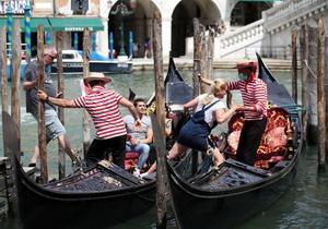 Dos gondoleros ayudan a unos turistas a subir a bordo, en Venecia.