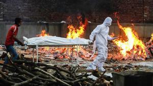 Un familiar de un fallecido por covid y un trabajador sanitario trasladan el cuerpo del finado para ser incinerado en un crematorio e Nueva Delhi.