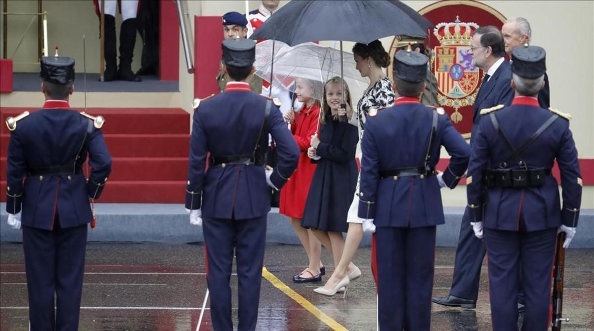 La reina Letizia, la princesade Asturias y la infanta Leonor,junto al presidente del Gobierno en funciones,Mariano Rajoy y el ministro de Defensa en funciones,Pedro Morenés, en el desfile militar del 12-O.