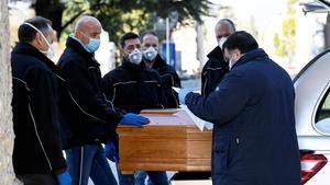 Hombres con mascarillas trasladan el féretro de un fallecido por coronavirus.