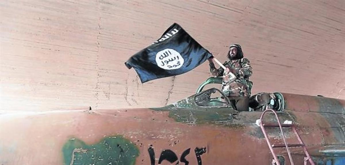 Un militante del Estado islámico ondea una bandera del califato en Raqqa (Siria).