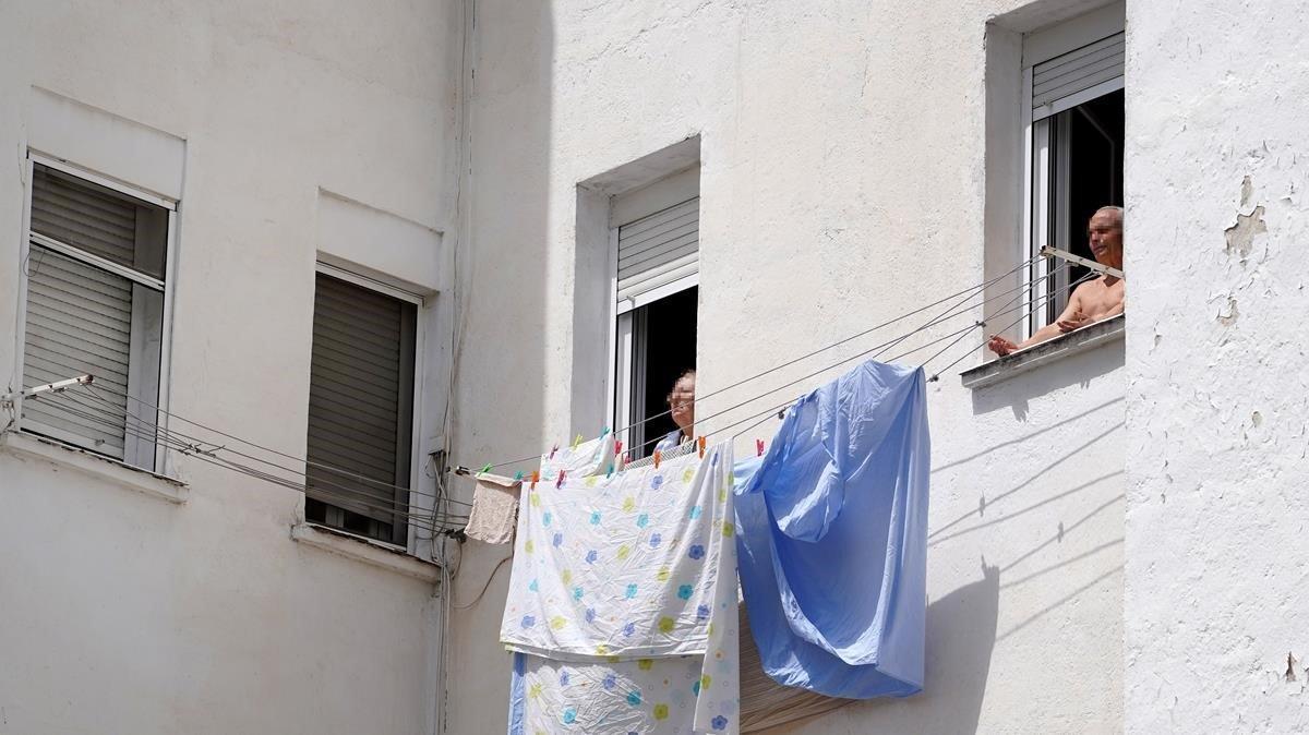 Dos personas mayores toman el sol en la ventana vivienda en Madrid.