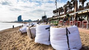 Una veintena de sacos protegen los chiringuitos y demás mobiliario de la playa de la Barceloneta