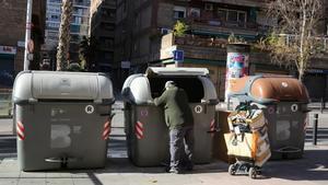 Un hombre recoge basura en unos contenedores de Barcelona, el año pasado.