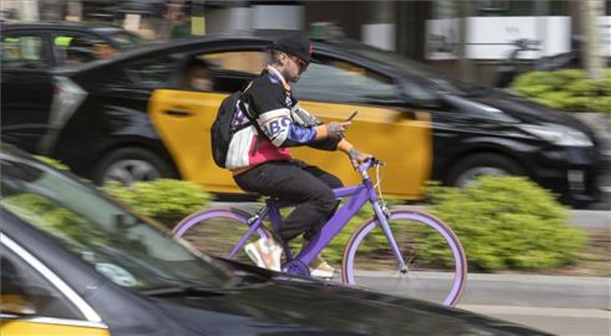 Un hombre circula con su bicicleta mirando su móvil por el carril bici de la avenida Diagonal de Barcelona.