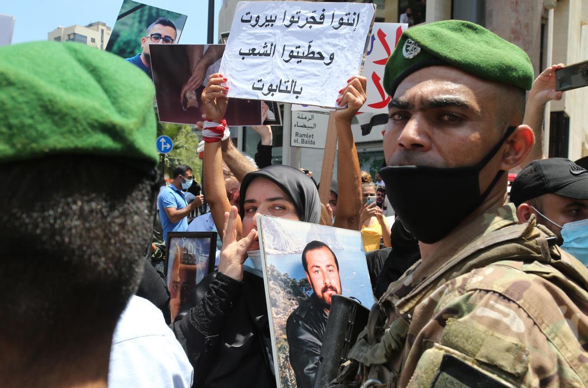 Una mujer sostiene un retrato de un familiar fallecido frente a los soldados que bloquean el acceso al Palacio Ain al-Tineh, la residencia del presidente del Parlamento, en Beirut, Líbano.