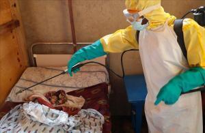 Un trabajador sanitario rocía con spray un niño que se sospecha ha muerto de Ébola en la República Democrática del Congo.