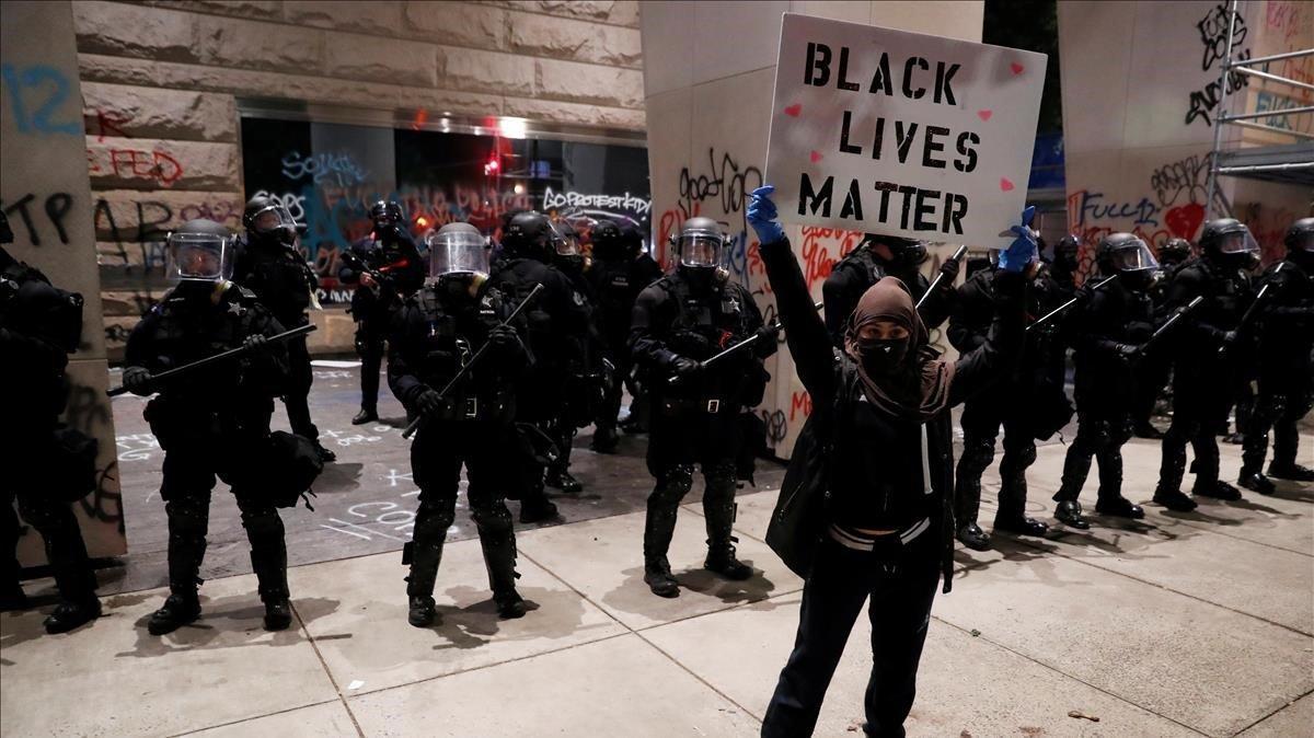 Una manifestante muestra un cartel con la frase en inglés La vida de los negros importa frente a un fila de policías en Portland.
