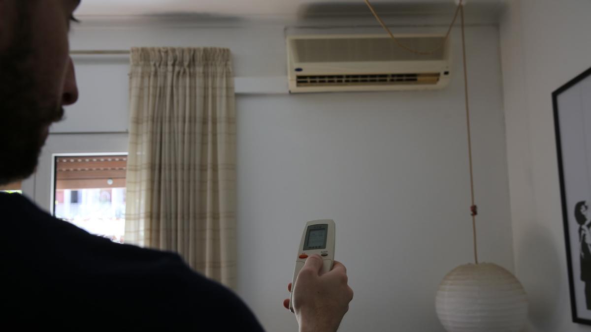 Un hombre enciende un aparato de aire acondicionado.